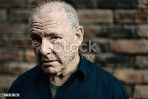 A slightly sinister looking senior man stares at camera looking suspicious.