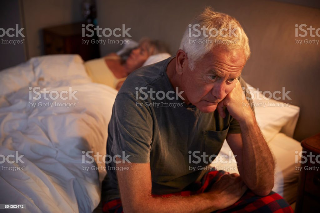 Worried Senior Man In Bed At Night Suffering With Insomnia stock photo