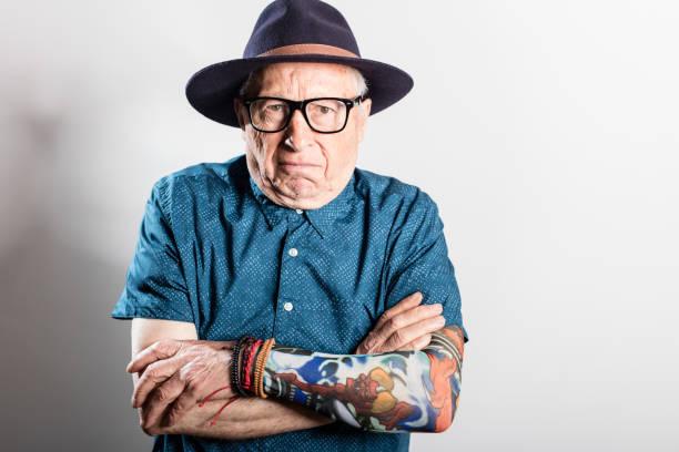 besorgt senior woman blick in die kamera, exemplar - alte tattoos stock-fotos und bilder
