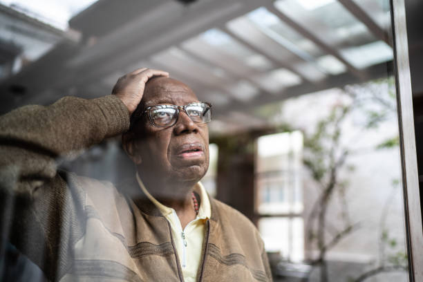 Worried senior man looking through the window at home stock photo