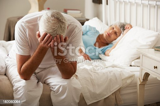 istock Worried Senior Man Sits On Bed Whilst Wife Sleeps 182060064