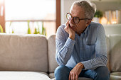 istock Worried senior man sitting alone in his home 1211839973