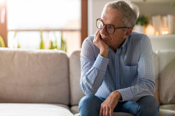 besorgter senior sitzt allein in seinem haus - depression stock-fotos und bilder