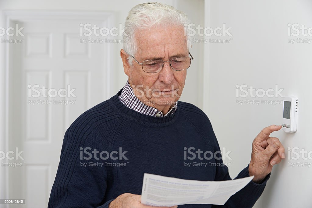 Worried Senior Man With Bill Turning Down Central Heating Thermo stock photo