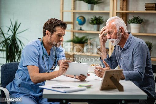 Mature man feeling concerned while talking to his doctor who is showing him medical test results on digital tablet.