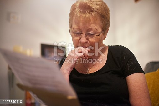 Senior woman looking slightly worried reading through letter