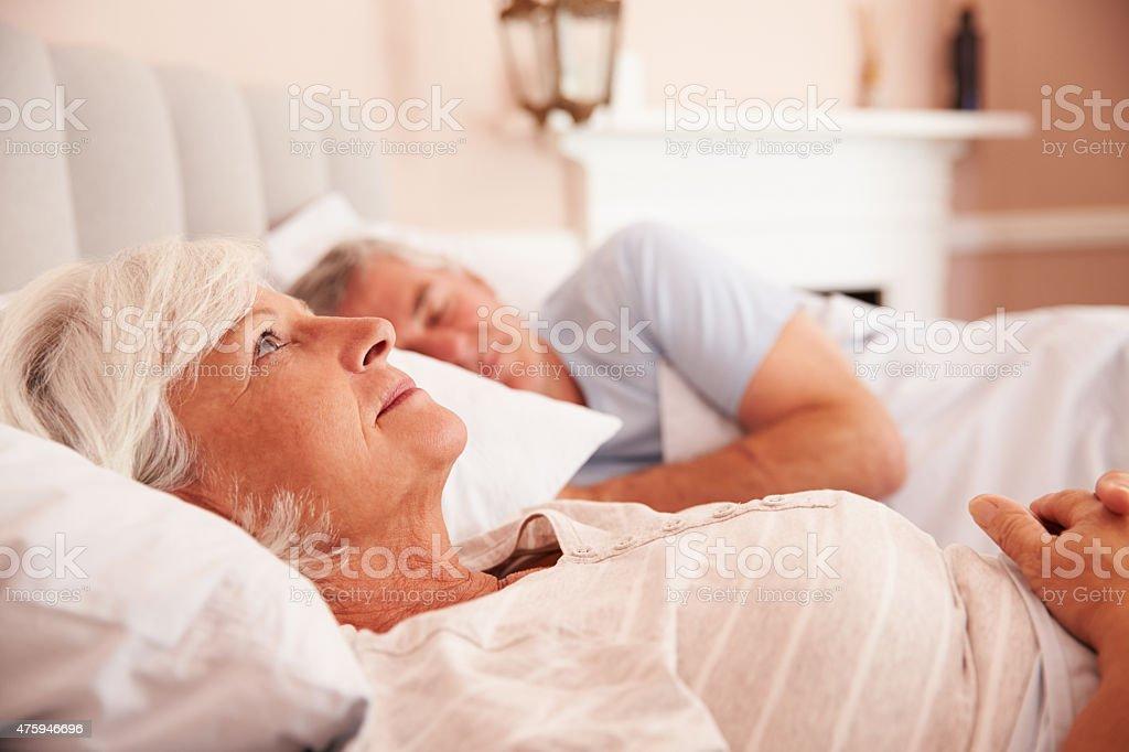 Worried Senior Woman Lying Awake In Bed stock photo