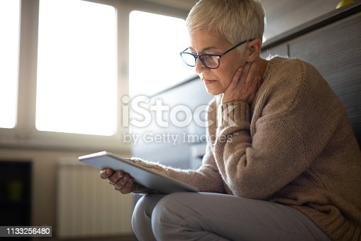 Serious senior woman using tablet computer indoors seems concerned