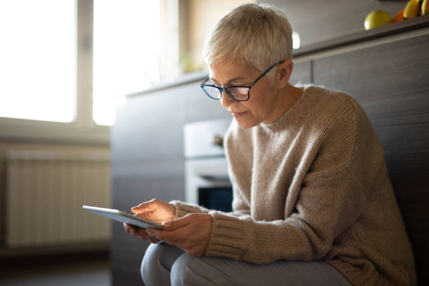 Worried senior woman reading an e-mail on tablet stock photo