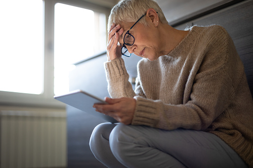 istock Worried senior woman reading an e-mail on tablet 1181284146