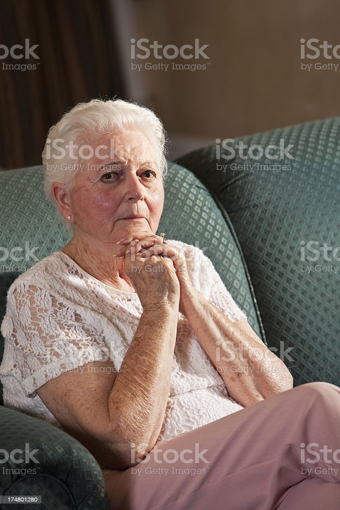 Worried senior woman sitting on couch stock photo