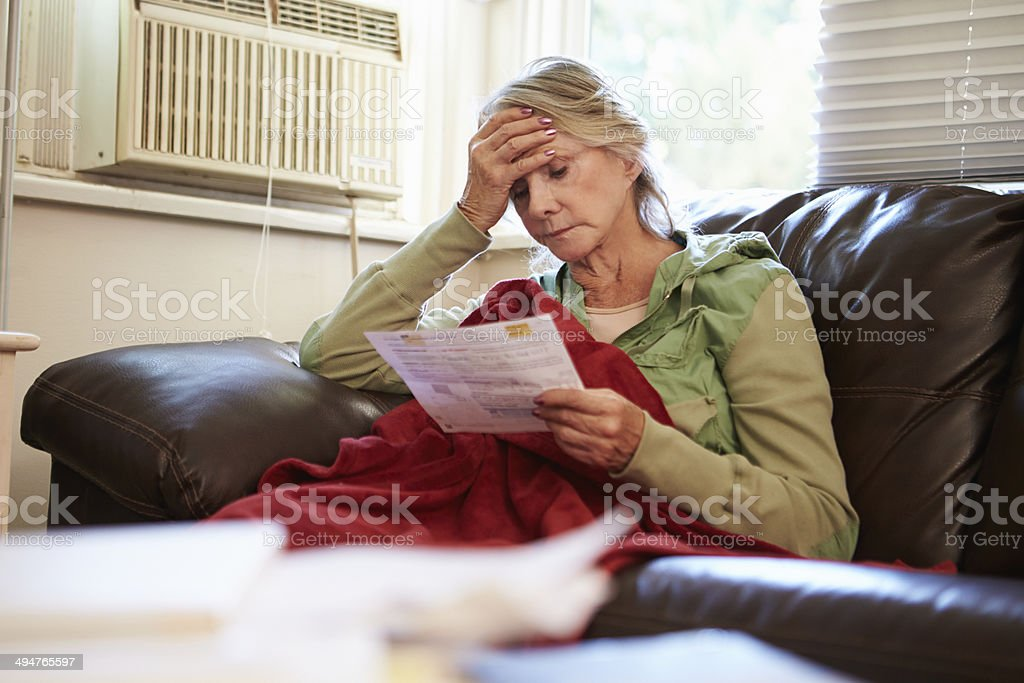 Worried Senior Woman Sitting On Sofa Looking At Bills stock photo