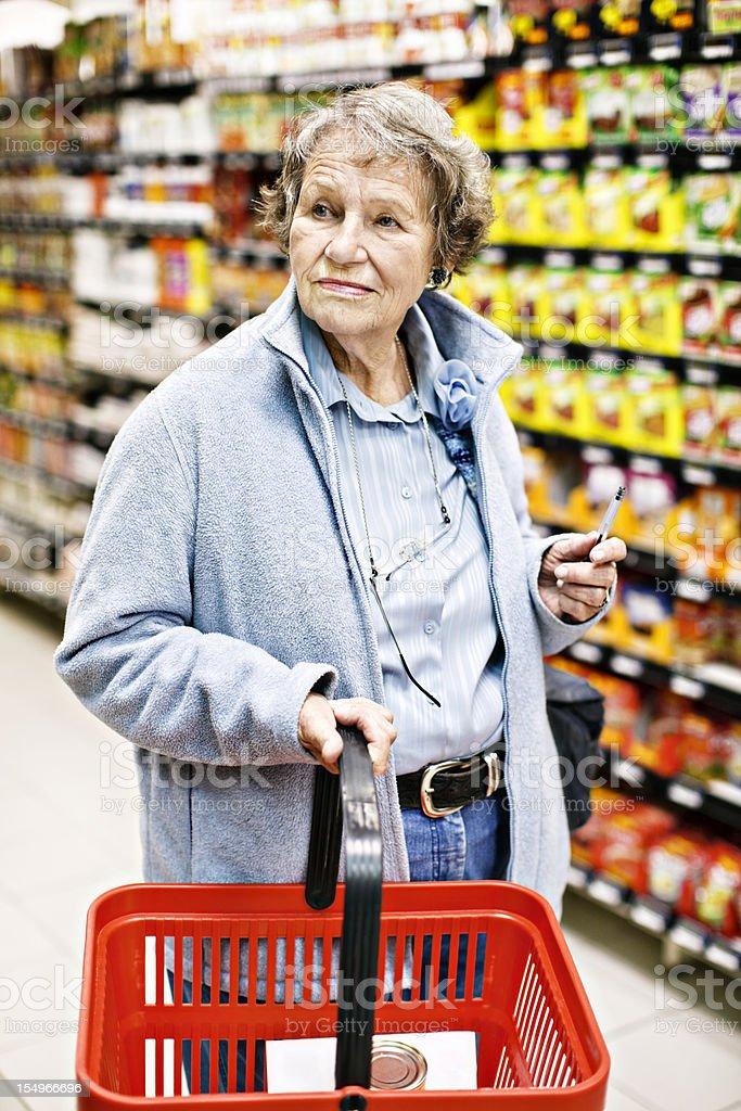 Worried senior woman supermarket shopper looks confused stock photo