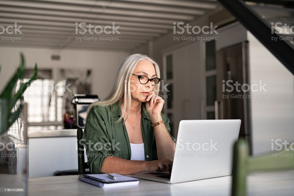 Worried senior woman using laptop Focused old woman with white hair at home using laptop. Senior stylish entrepreneur with notebook and pen wearing eyeglasses working on computer at home. Serious woman analyzing and managing domestic bills and home finance. 40-49 Years Stock Photo