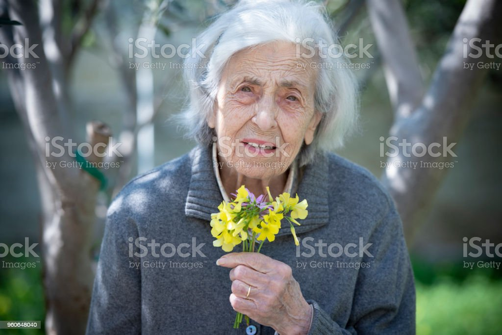 Worried senior woman with a little bunch of flowers - foto stock