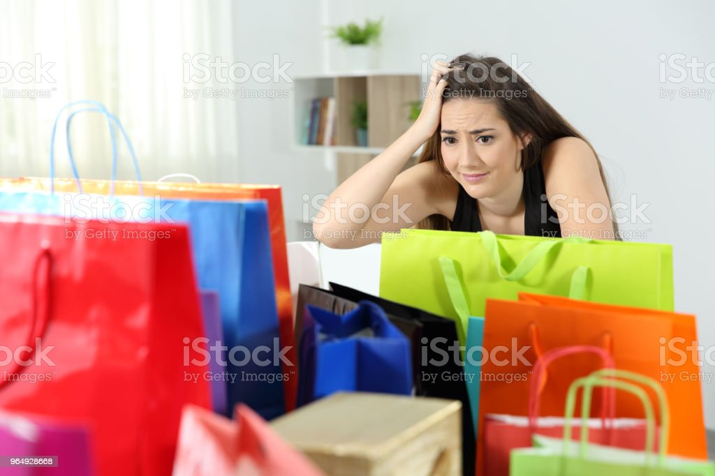 Worried shopaholic woman after multiple purchases stock photo