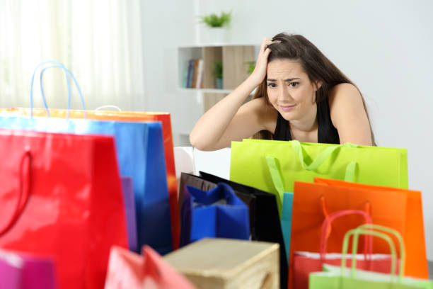 worried shopaholic woman after multiple purchases - attività commerciale foto e immagini stock