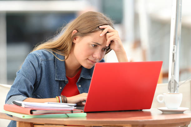 Worried student searching on line in a laptop stock photo