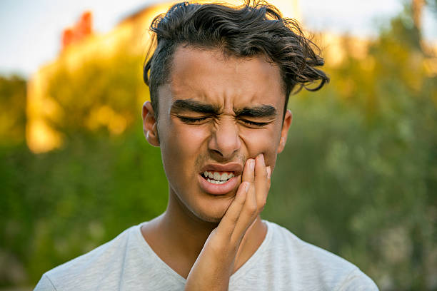 Worried teenage boy rubbing his mouth because of toothache stock photo