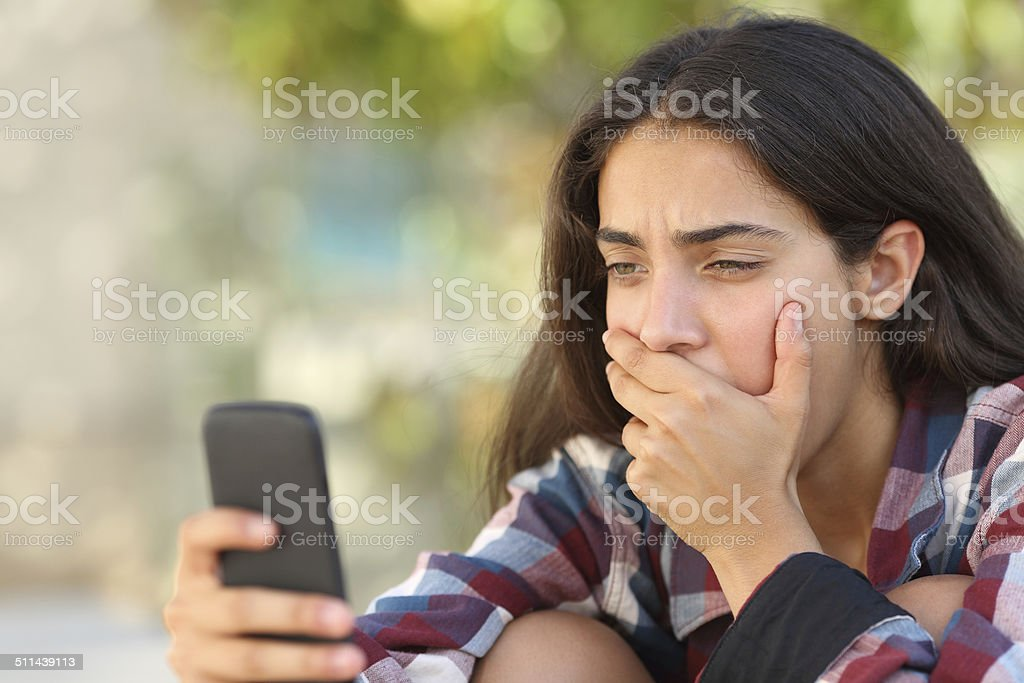 Worried teenager girl looking at her smart phone stock photo