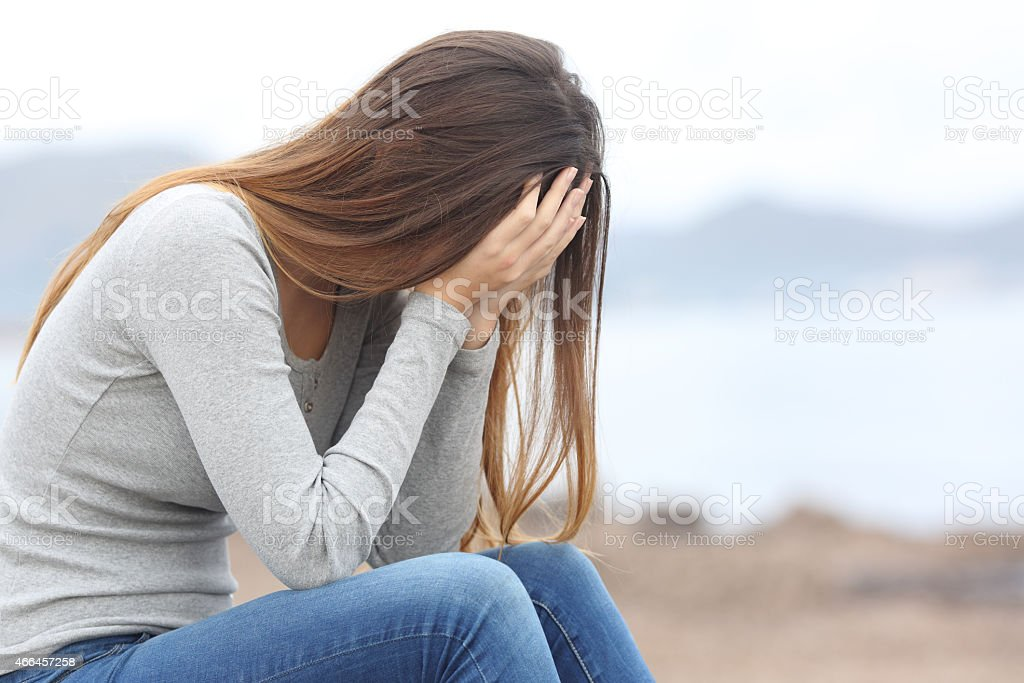 Worried teenager woman on the beach in winter stock photo