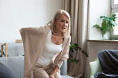 istock Worried upset mature woman feel hurt sudden back ache 1188934127