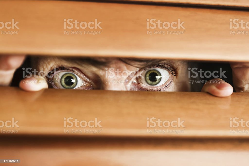 Worried wide-eyed old woman looks through wooden venetian blind stock photo
