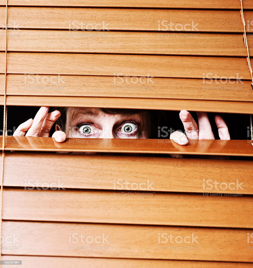 Worried wide-eyed older woman peeps through slats of wooden blind stock photo