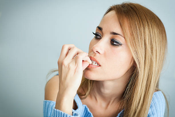 worried woman biting her nails stock photo