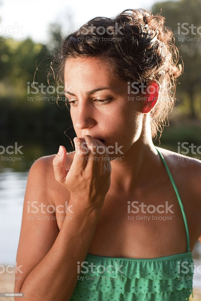 Worried woman biting nails stock photo