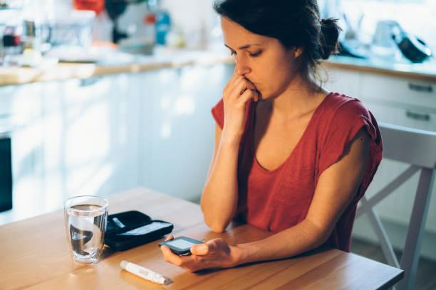 besorgte frau aus den blutzucker-testergebnissen - hyperglycemia stock-fotos und bilder