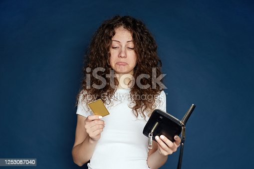 Internet banking, commerce concept. Upset young curly haired female with poring lips, can not use credit card for online shopping, has not enough money on her account. Disappointed female indoors.