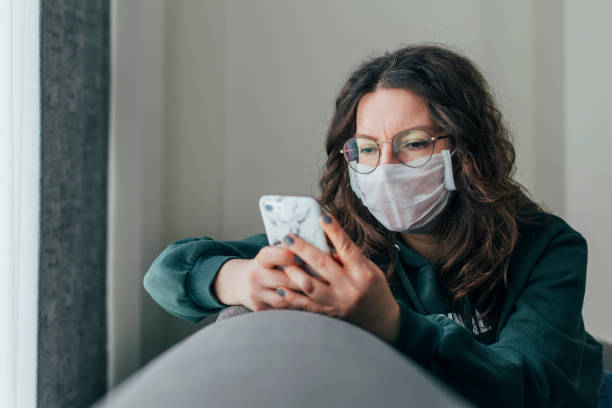 Worried Woman is Reading News on Phone Young woman covering her face with surgical mask and using smartphone to find information about coronavirus spread on internet pandemic illness stock pictures, royalty-free photos & images