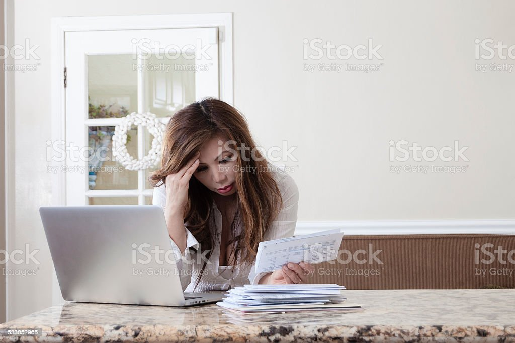 Worried woman looking at bills next to Macbook in kitchen stock photo