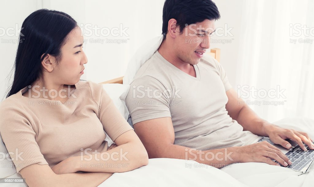 Worried Woman Lying Next To Her Trying To Peek At Screen Cheating And Infidelity