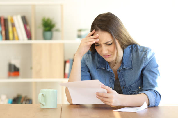 Worried woman reading bad news in a letter stock photo