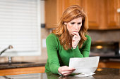 istock Worried woman reading bank statement 183763647