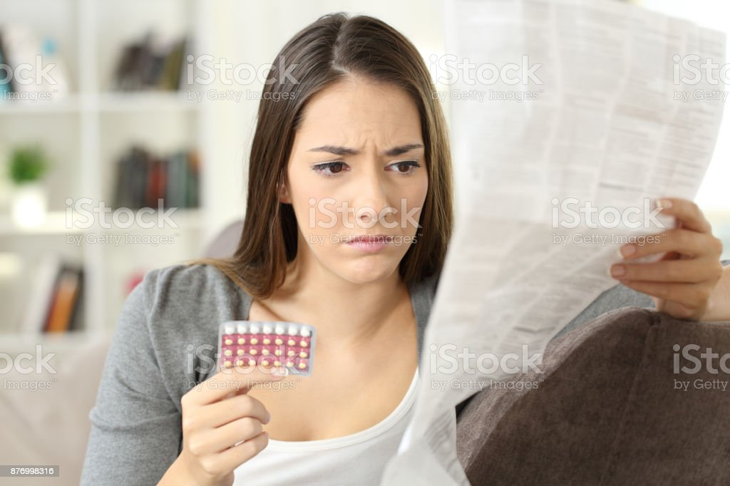 Worried woman reading contraceptive pills leaflet stock photo