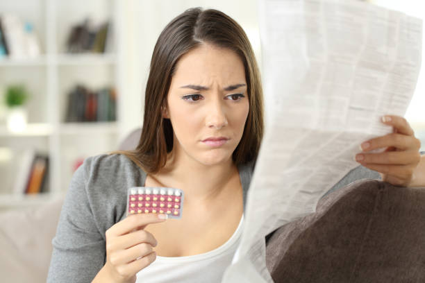 worried woman reading contraceptive pills leaflet - birth control pill stock photos and pictures