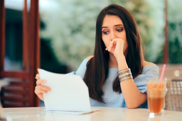 Besorgte Frau liest Dokumentenpapiere in einem Restaurant – Foto