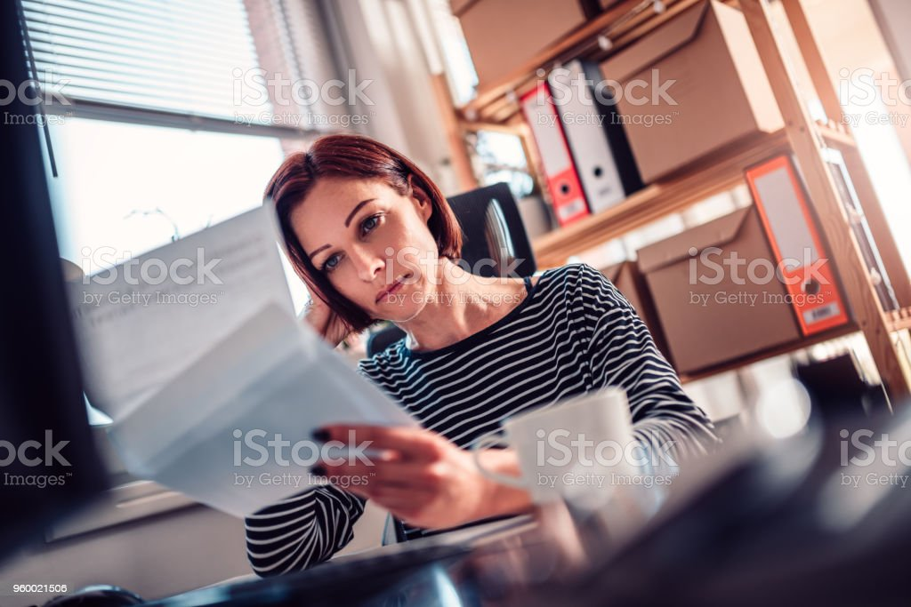 Worried woman reading mail at the office stock photo