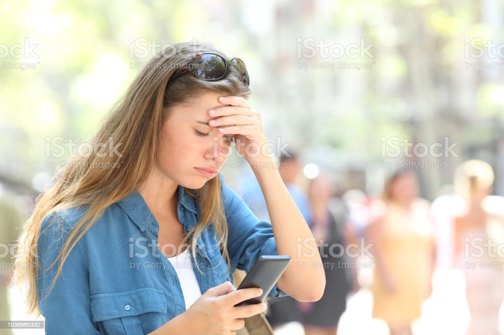Worried woman reading online smart phone content in the street