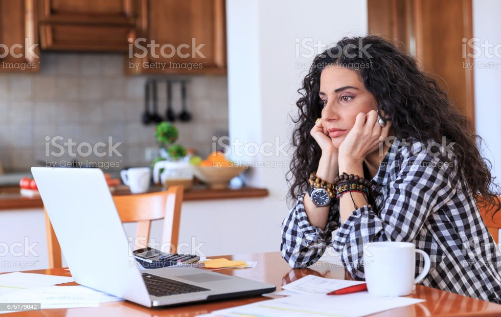 Worried woman sitting at home stock photo