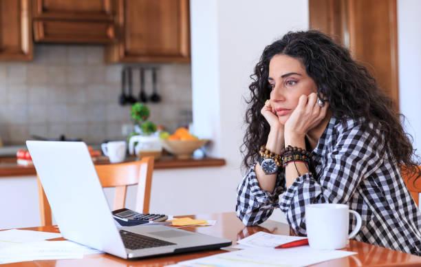 femme inquiète assis à la maison - prêts immobiliers et crédits photos et images de collection
