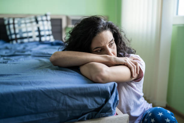 worried woman sitting on floor next to bed - crisi foto e immagini stock
