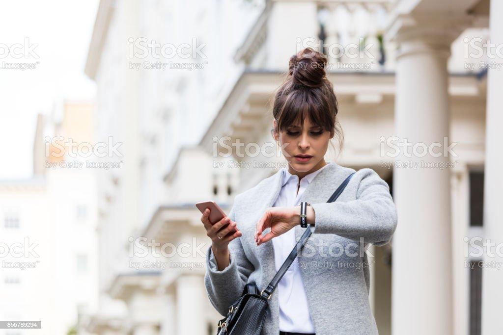 Besorgt Frau mit Smartphone vor Stadthaus Lizenzfreies stock-foto