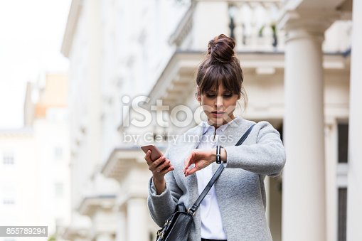 istock Worried woman standing with smart phone in front of city house 855789294
