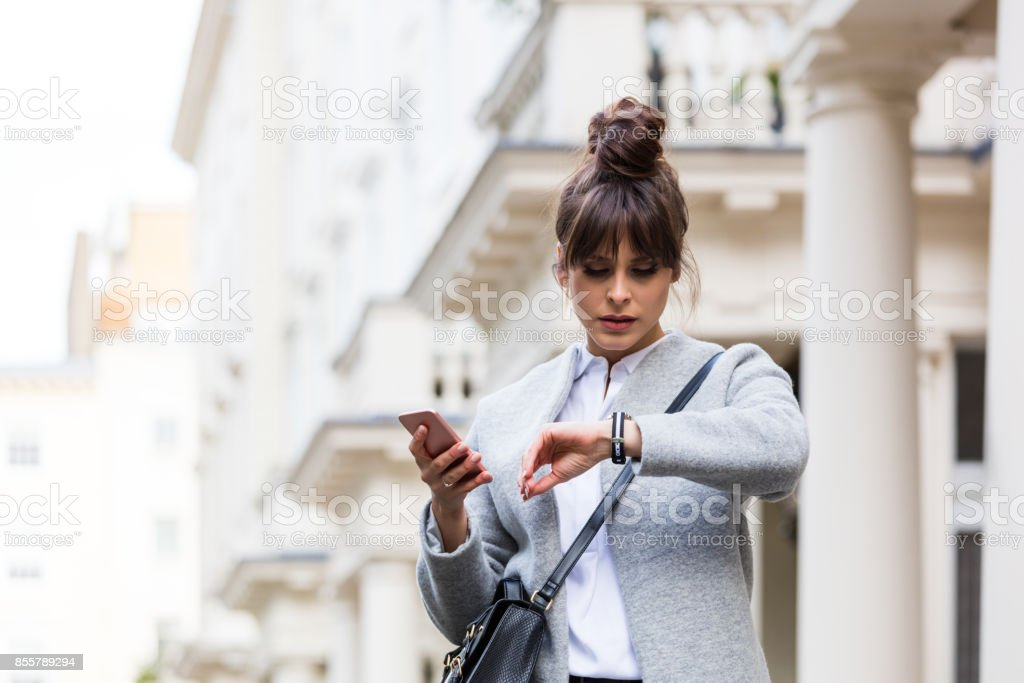 Worried woman standing with smart phone in front of city house stock photo