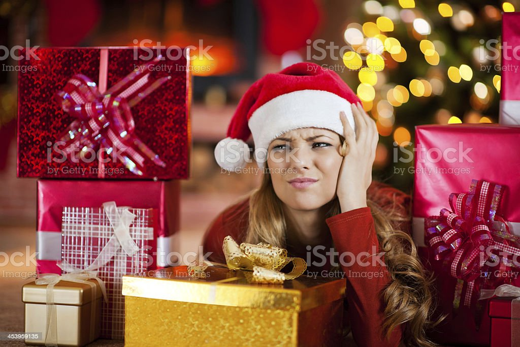 Worried woman surrounded by Christmas presents. stock photo