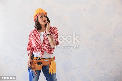 istock Worried woman talking on smart phone on contruction site 639653530